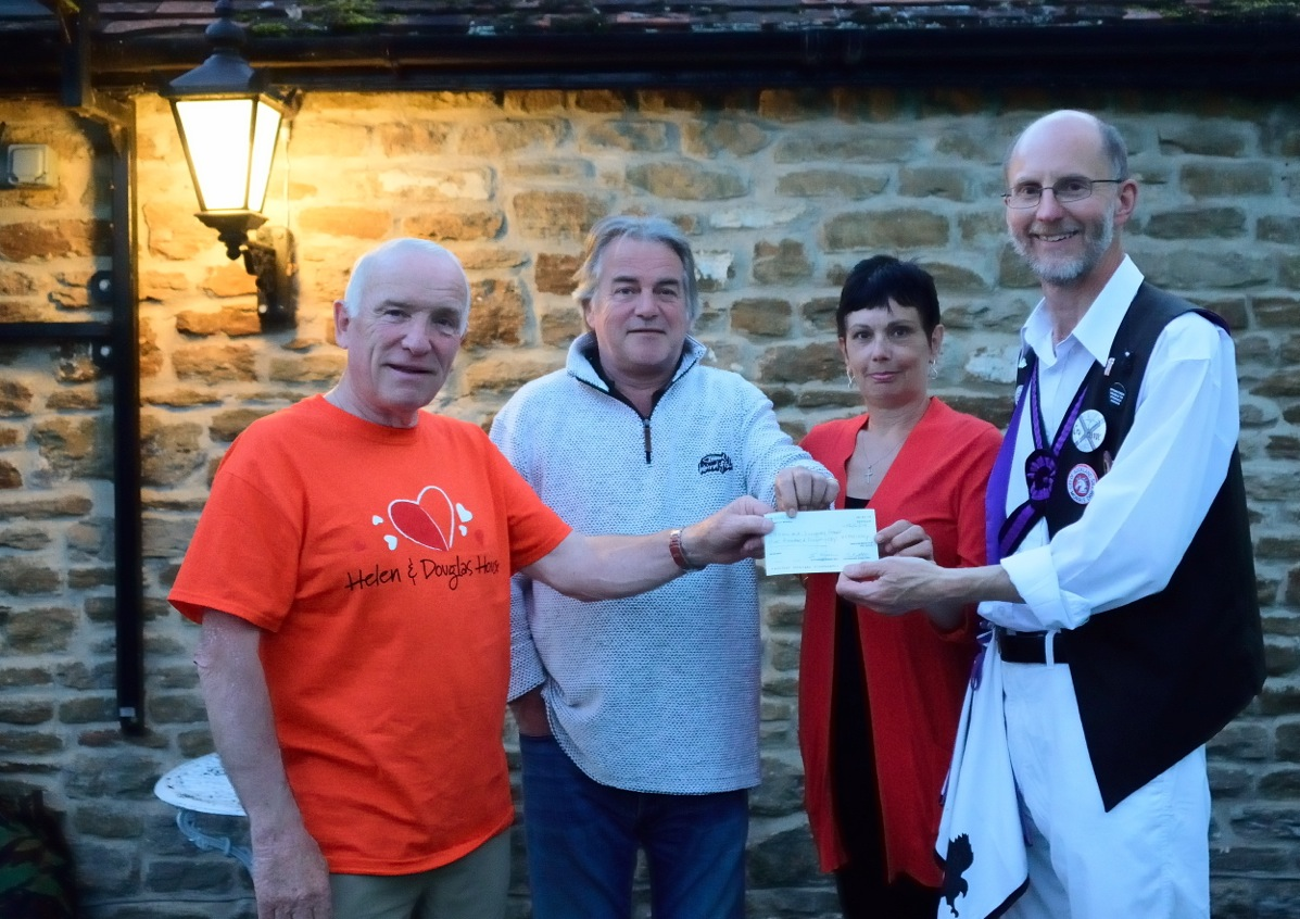 From right to left, The Squire, Karen, and Phil present a cheque to Peter West of Helen & Douglas House.